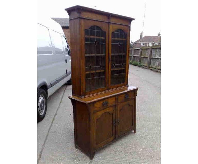 An Arts & Crafts oak bookcase with a flaring cornice and shaped supports below, teardrop stain glass to the leaded doors with arched tops, and a pair of drawers and a cupboard below, also with arched top panels. Measures: Height 79
