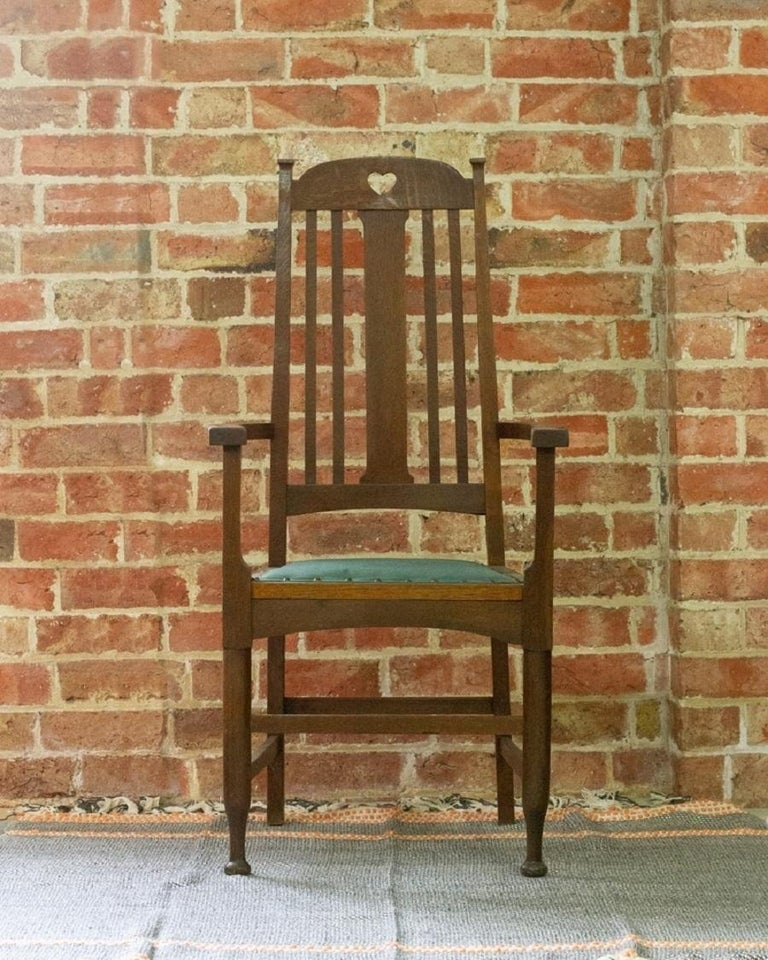An arts and crafts carver chair/occasional chair made in oak with heart detail and green plain linen upholstered seat with matching trim and dome nails. The chair is overall in good condition with a few age related marks.