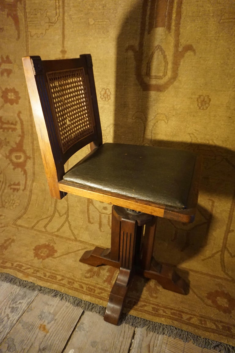 Quaint and compact Arts & Crafts Mahogany swivel chair with original leather and cane. This was a high quality manufacturer (stamped WD Allison Company) based out of Indianapolis with offices in major US cities that specialized in furniture for