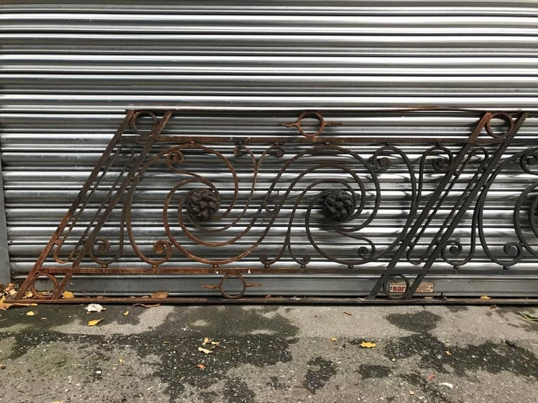 An Arts & Crafts style decorative cast and wrought iron angular staircase Bannister with circular radiating details centered with stylized floral leaf details.