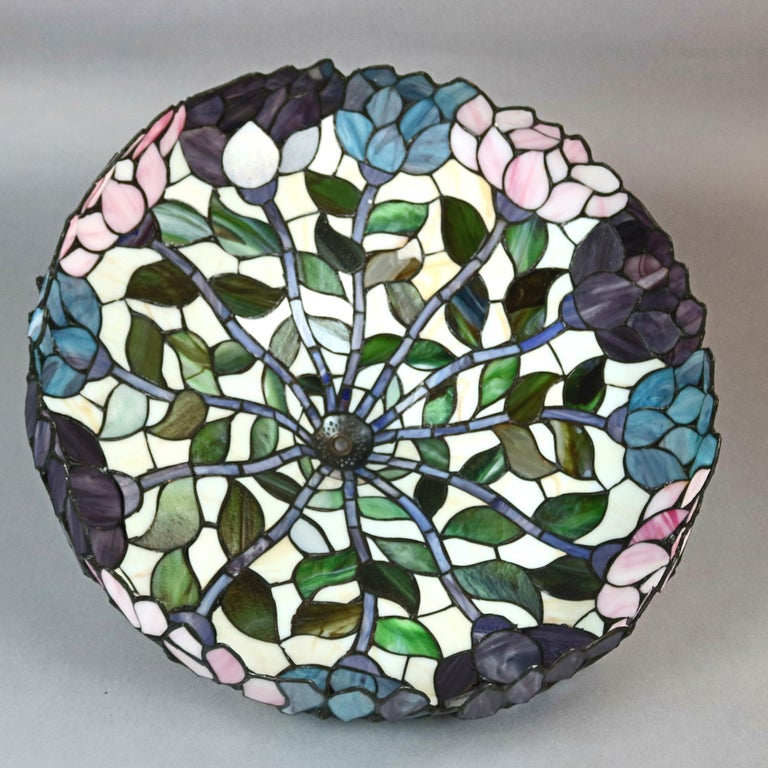 An Arts & Crafts Tiffany School table lamp offers parasol form shade with leaded slag glass floral mosaic raised on double socket foliate cast base, elements of Art Nouveau, 20th century  ***DELIVERY NOTICE – Due to COVID-19 we are employing