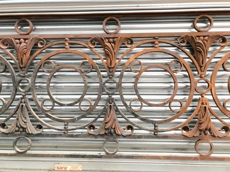 An Arts & Crafts style late Victorian decorative cast and wrought iron railing or balcony banister rail with circular and small ball details and stylized floral leaf details with a nicely shaped hand rail to the top. Measures: Length 122 inches,