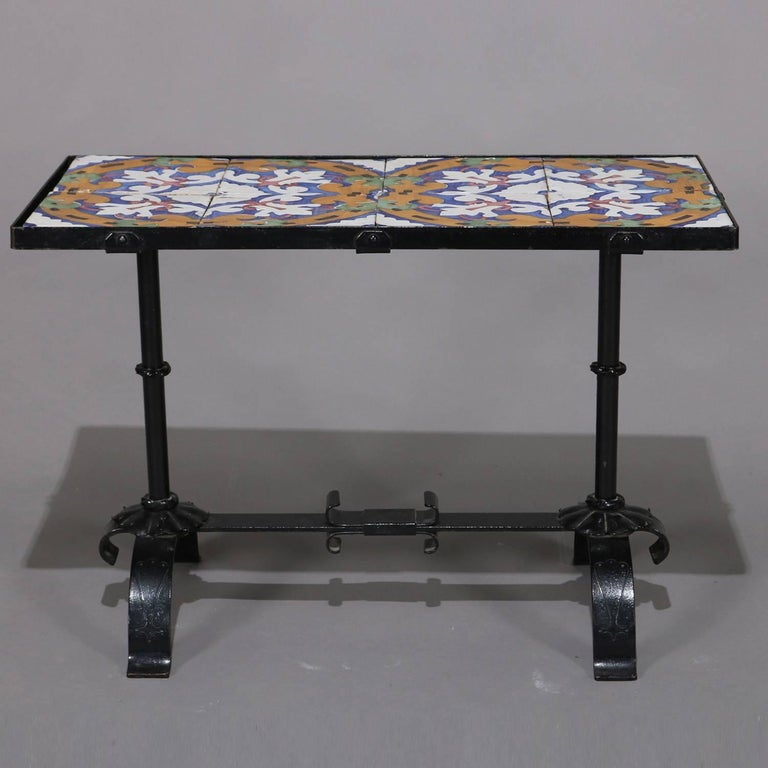 Arts & Crafts Yellin school table features wrought iron construction in trestle form with California stylized floral enameled tile top, circa 1920.  Measures: 22