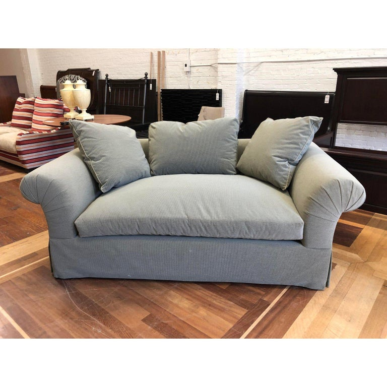A custom lounge sofa by A. Rudin. A rolled arm deep luxe depth for comfort. Upholstered in Rogers & Goffigon- Hash Stone Dust fabric. The trimming of the pillows are a Samuel & Sons Warwick Twist for with tape. A single seat cushion accompanied with