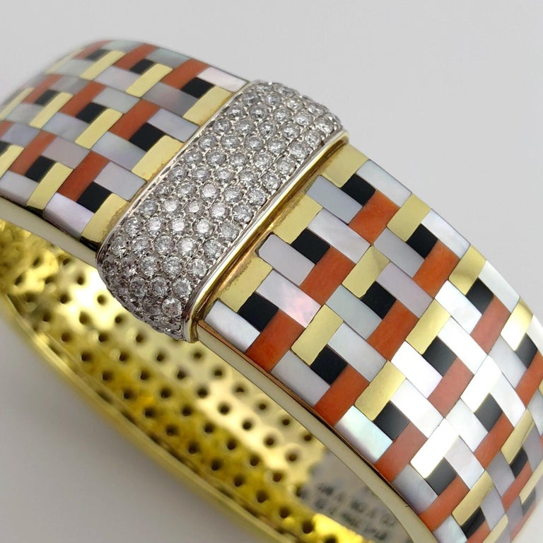 This stunning Asch Grossbardt 18 Karat yellow gold bracelet is inlaid with Coral, Black Onyx, and Mother of Pearl. Intricately cut geometric shaped stones form a basket weave art deco inspired pattern. The center of the bracelet is set with with 87
