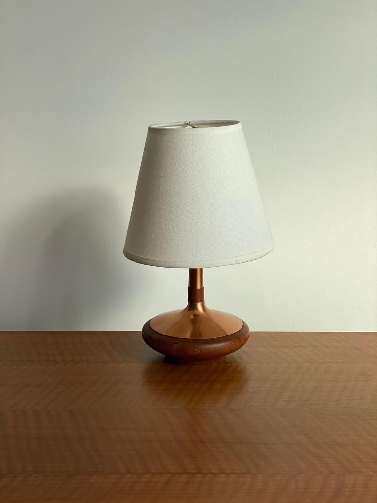 A small table lamp or desk light. Designed and produced by ASEA, Sweden, 1960s. Turned teak and copper details. Stamped with makers mark and Swedish production label.  Lampshade attached on lightbulb-clip is not included in purchase. Dimensions