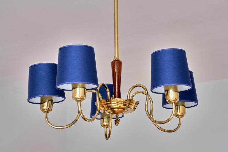 This elegant brass chandelier was produced by ASEA Belysning in Sweden in the 1940s. The brass stem leading to a wooden column in lacquered elm and a brass receiver bow with a crown finial detail. The five arms and tubular lamp holders are in brass