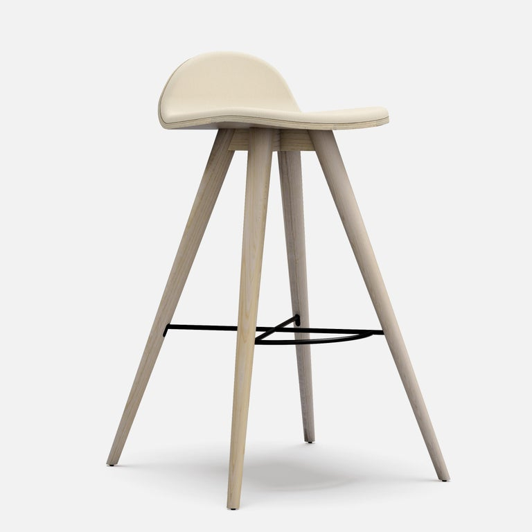 Ash and fabric contemporary counter stool. Dimensions: W 49 x D 46 x H 79 cm Materials: Ash and fabric  Structure also available in beech, ash, oak and mix wood Seat also available in fabric, leather and corkfabric.