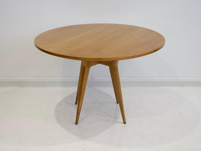 Round table from the 1950's, Italy, made of ash wood. Design in the style of Gio Ponti. Four legs with brass socks. Slight marks on wood on the feet.