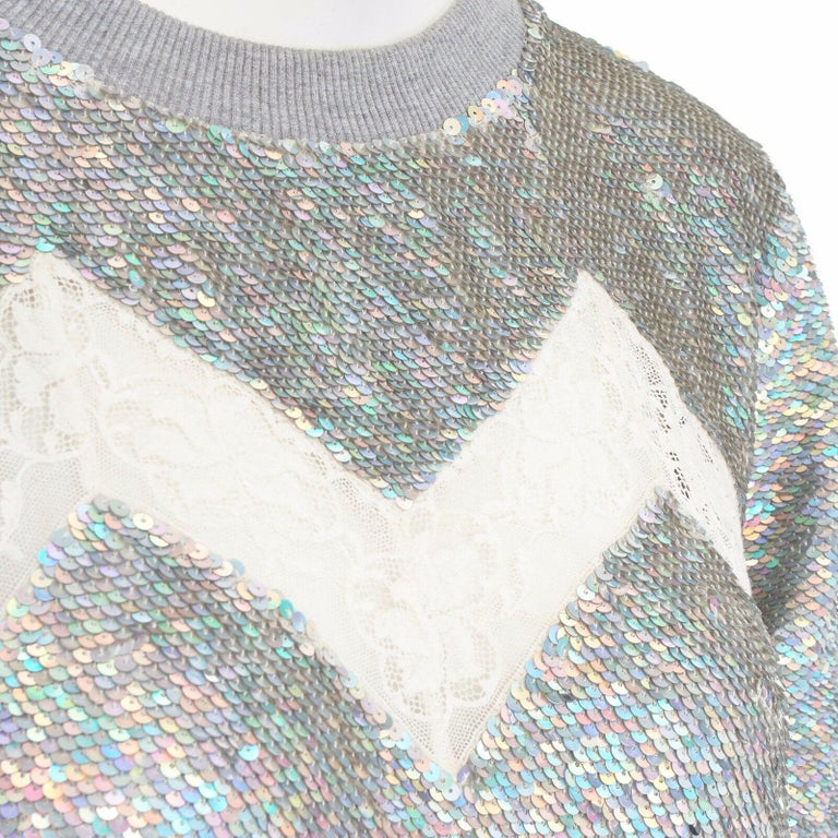 ASHISH iridescent silver sequin white lace sweater top XS US0 UK6 IT38 FR34  ASHISH Grey silk georgette, cototn, spandex, nylon . Iridescent holographic silver sequins embellished throughout . Light grey ribbed neckline . White lace insert at chest
