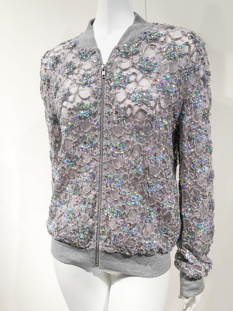 Sporty gray lace zippered bomber jacket with iridescent sequin hand embellishments by Ashish. Knit cuffs, collar and hem. Size Medium. Condition New without tags. Excellent condition.