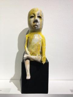 Ceramic figure on wood block: 'Varada mudra boy'
