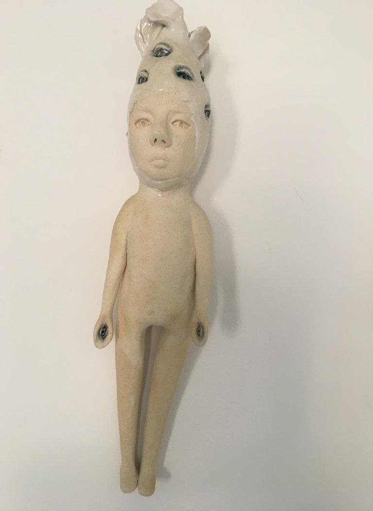 Ashley Benton Figurative Sculpture - Ceramic wall hanging sculpture: 'Continue to seek'