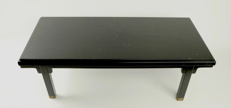 Diminutive and graphic Asia Modern coffee table having all-over black finish and brass CAP feet. The finish shows cosmetic wear, light scratching and signs of age and use. Manufacture attributed to Baker Furniture, unsigned.