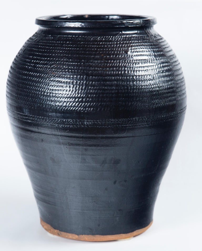 Asian black glaze ceramic storage jar, 20th century. Large size container with overall incised design.