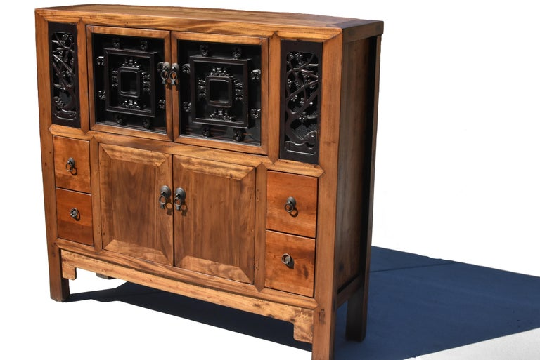 A beautiful Chinese book cabinet, made of solid wood in mitered tenon and mortise construction. Top doors and side panels feature carved antique screens backed by mesh and glass. The carvings depict plum tree blossoms and butterflies. The bottom