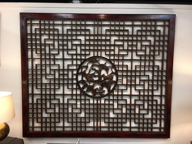 Stunning vintage Chinese large mahogany and elmwood latticed wall sculpture that is one of a kind. It is large, dimensions are below, and has open fretwork throughout. The center has carvings that are nothing short of magnificent.