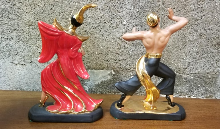 A 1950s pair of ceramic oriental dancing figures in the manner of Hedi Schoop. Classic 1950s decor with primary colors of red, black and gold. Excellent original condition. Unknown maker.  Dimensions are for each figure.