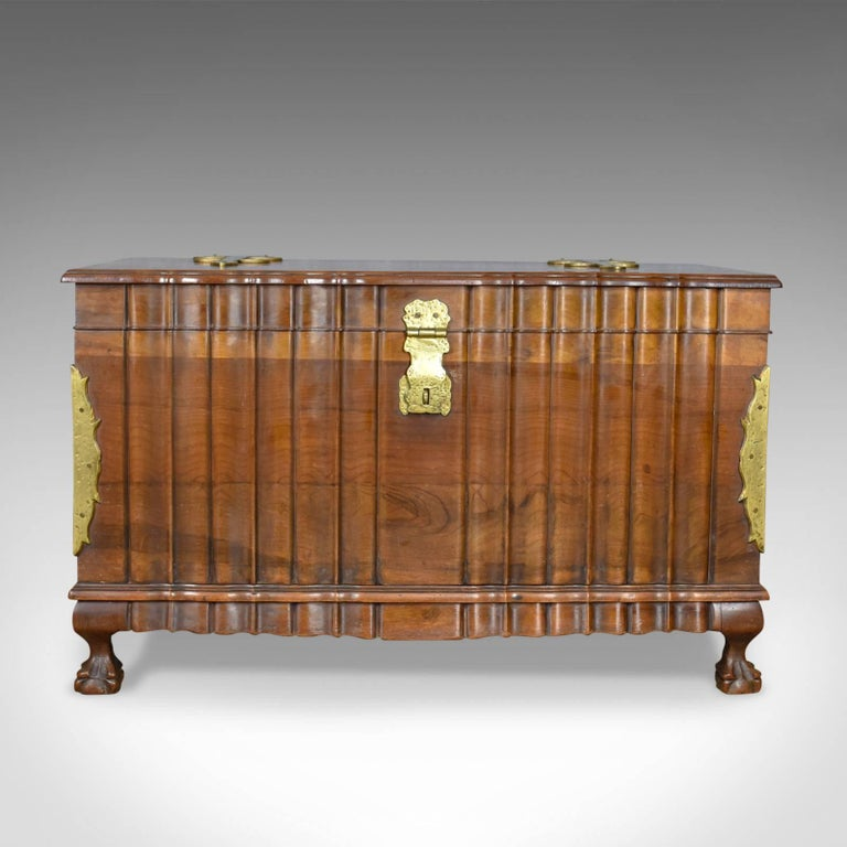This is an Asian hardwood trunk, a bronzed metal mounted chest or coffer dating to the late 20th century.  Of quality craftsmanship and stock Attractive variegated grain interest in caramel hues In rippled form dressed with hammered bronzed