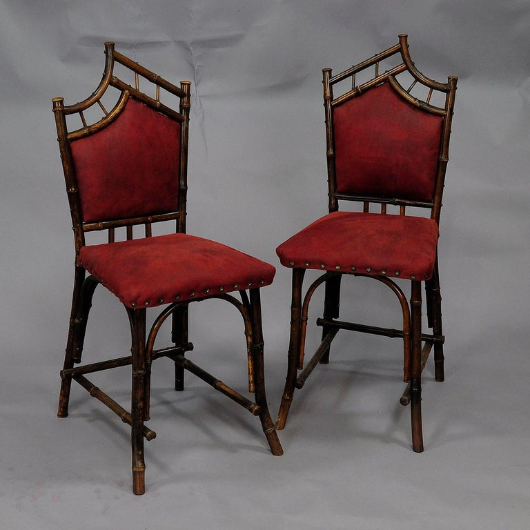A delicate set of bamboo furniture in Asiatic design. Consisting of a table and two chairs. Made of several bamboo pieces circa 1930s. Upholstery renewed.   Chairs measures:  Width: 14.6
