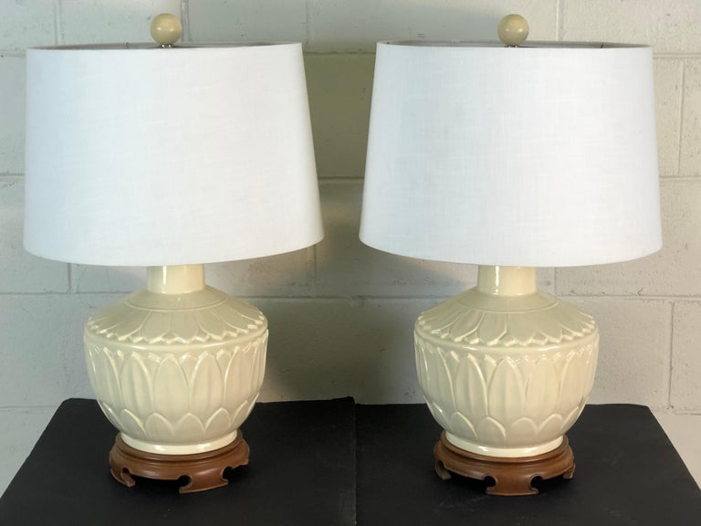 "1960s pair of white Asian style ceramic lamps with lotus flowers and a round wood base. The ceramic lamps are also round and the leaves cover the base of the lamp. The lamps are wired for the US and in working condition. Harp: 4.25"" diameter x 10"""