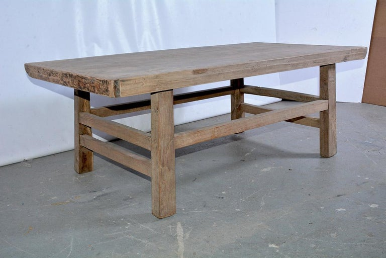 The rustic Asian coffee table is constructed with a teak wood plank top held by breadboard ends. The table is secured with pegged legs and stretchers - doubled at the ends. Ready to appear in an informal setting or on a porch. Great proportions.