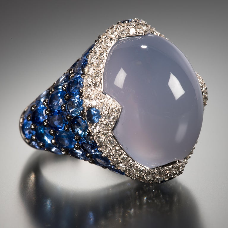 Asprey demonstrates how stones can work together to create a piece that is truly exceptional. The center stone of this ring is a beautiful blue 22.47 carat cabochon chalcedony. It is enhanced by a ring of lively diamonds and an exposed shank of 8.97