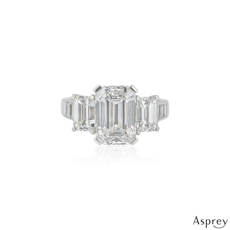 An exquisite diamond ring in platinum by Asprey. The ring is set to the centre with a 4.30ct emerald cut diamond in a classic 4 claw setting, the diamond is H colour and VVS2 in clarity. There are a further two, claw set emerald cut diamonds