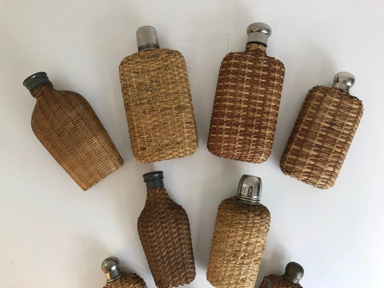 An assembled collection of nine vintage handwoven wicker flasks. Collection includes some wicker over glass, pewter, and silver, early 20th century. Largest measures: 7