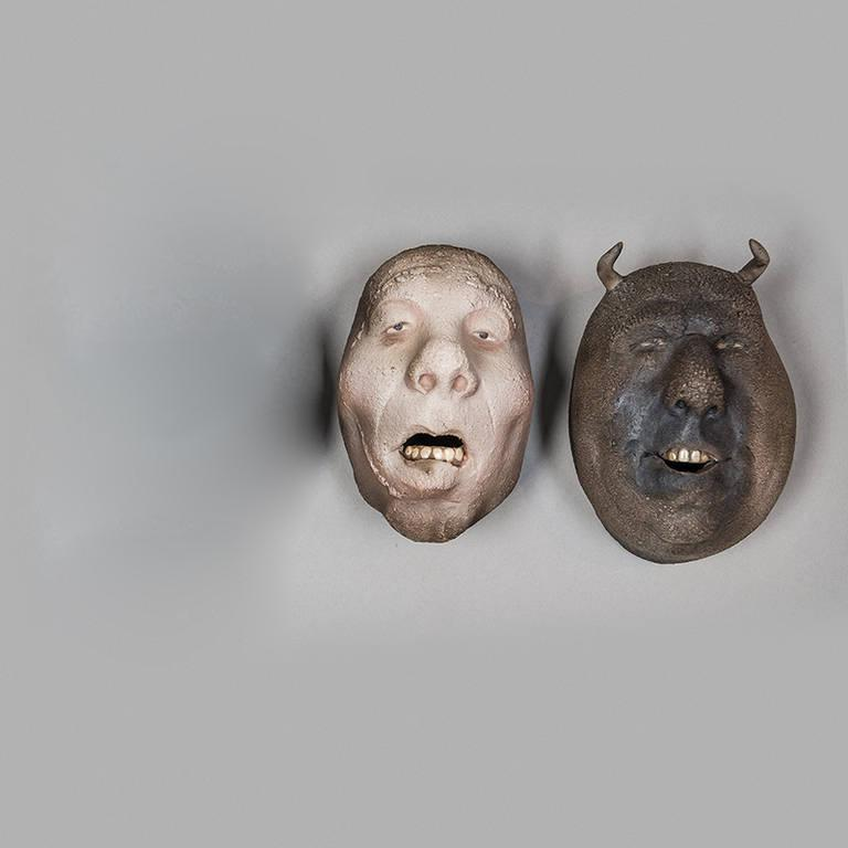 Assorted Raku fired faces, all with their own expressions, happy or sad, strong and sure, tragic or comic, by Johan Thunell. Raku is a pottery technique in which pots are raw-glazed at a low temperature then taken red-hot from the kiln and plunged