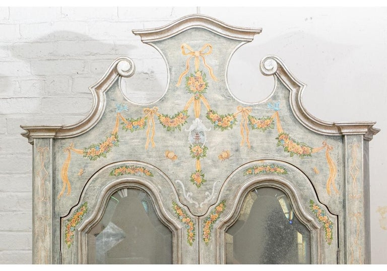 A tall custom Venetian baroque shaped frame, the double doors with inset beveled antiqued mirrors open to two shelves. The slant front opens to drawers and a cubby hole. The lower cabinet with three long drawers. Overall distressed look green/gray