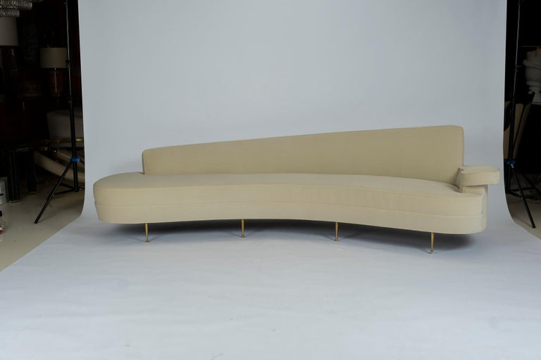 A magnificent asymmetrical curved back sofa upholstered in a creamy ecru velvet. This beautiful sofa is supported by solid brass sabots. We stripped the original 1950s Federico Munari Italian sofa down to its frame and copied it to exact