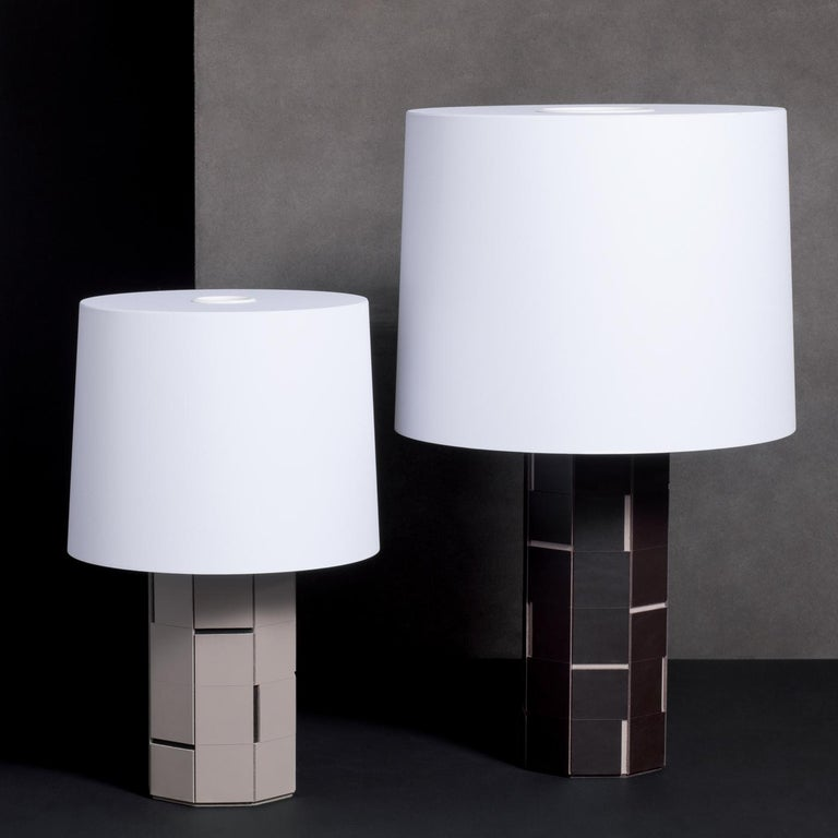 This unique table lamp, part of the Atari collection, will look right at home with any style. It features a base made of saddle leather white tiles with black grooves and a white shade that diffuses a soft light. The overall effect is of textural