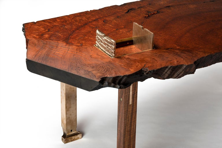 The Athol desk by Taylor Donsker features a live edge pommele old growth redwood slab with recessed cast bronze tree bark doors opening to a concealed compartment. Three interlocking, solid musical grade Oregon walnut legs feature sculpted cast
