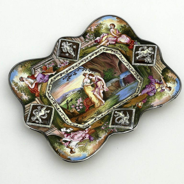 A pretty antique silver mounted Viennese enamel dish. This shaped rectangular dish features gorgeous enamel imaged across the entire top surface. The underside has a lovely monochrome scene surrounded by a subtle patterned border. The Interior
