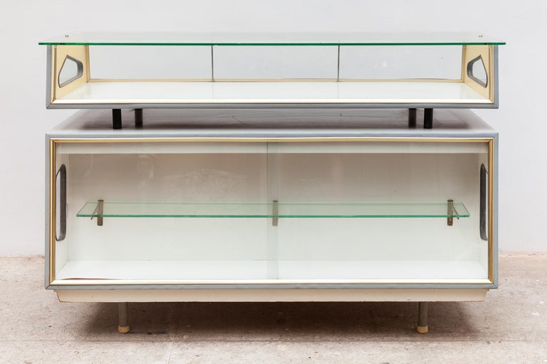 Vintage midcentury vitrine by Haasdijk, Rotterdam. Atomic era design in gray and yellow with gold accents. The front features an enclosed vitrine with shelf, a top display of glass which is open to the backside. The back has a drawer and key,