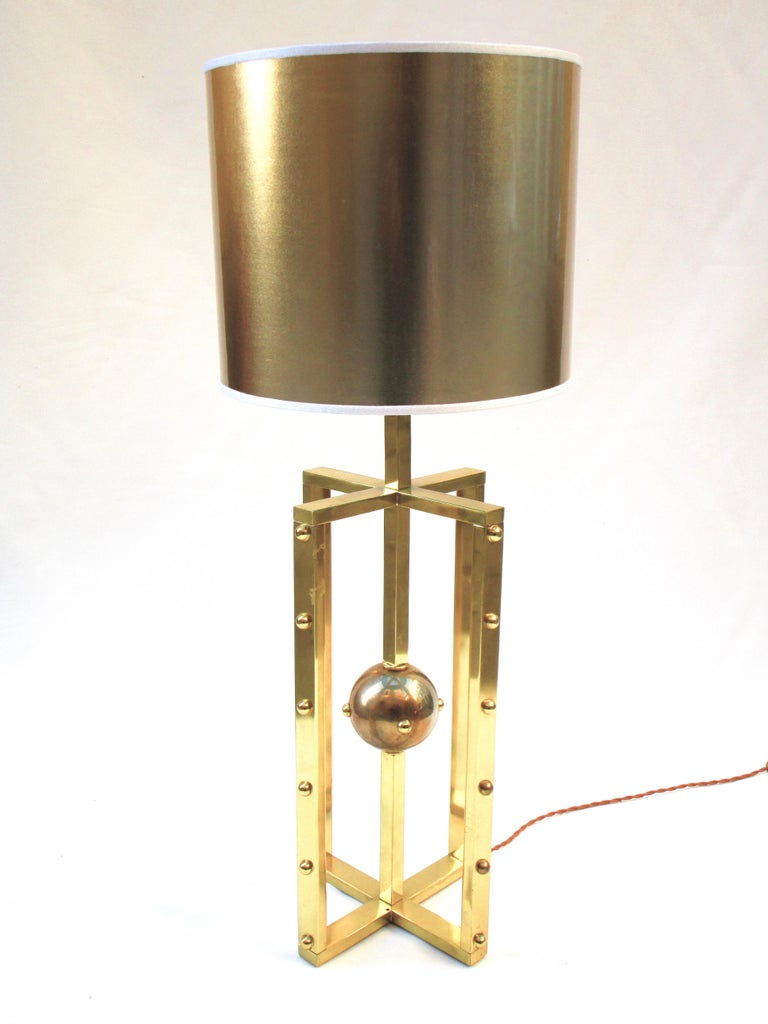 This elegant lamp is inspired by the structure of the atom and features a brass structure brushed in gold.  Structure: Painted polished brass.  Transparent, lampshade in PVC gold with a Turquoise interior.   Designed by Nicola