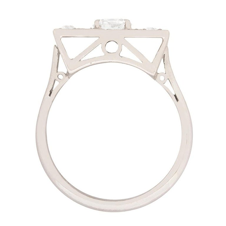 In the centre of this art deco ring is a 0.55 carat transitional cut diamond. It has been claw set and is surrounded by a collection of old cut and 8-cut diamonds within the square cluster design. The additional diamonds have a combined weight of
