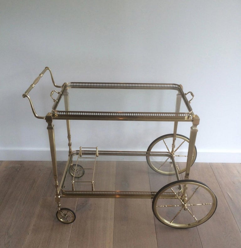 This neoclassical bar cart is made of brass with glass shelves. The quality of this drinks trolley is really good. It has fluted legs, large wheels in front and small ones on the back and has two removable trays. This is a French work, attributed to