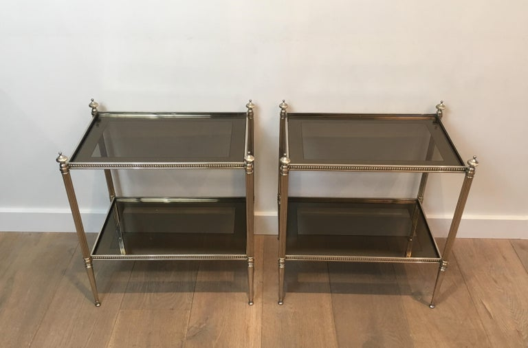 This very nice pair of neoclassical style side tables is made of silver plated with bronze glass shelves surrounded by a silver-mirrored line. This is a very nice French work, attributed to Maison Jansen, circa 1960.
