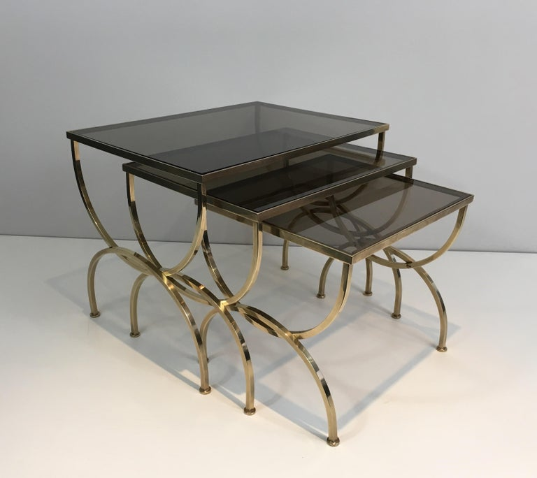This nice set of three neoclassical nesting tables is made of brass with smoked glass shelves. The design is very nice and chic with simple lines on the base of the tables.