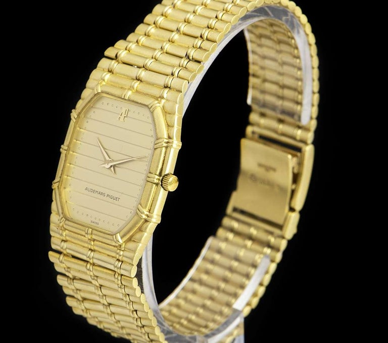 An 18k Yellow Gold Bamboo Vintage Gents Wristwatch, champagne tapestry dial, a fixed 18k yellow gold bezel, an 18k yellow gold integrated bracelet with an 18k yellow gold jewellery style clasp, mineral glass, quartz movement, in excellent condition,