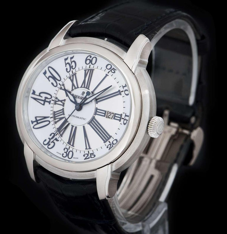 An 18k White Gold Millenary Gents Wristwatch, white lacquered dial with blue printed arabic numbers, satin-brushed off-centred disc with applied roman numerals, date at 3 0'clock, a fixed 18k white gold bezel, an original black leather strap with an