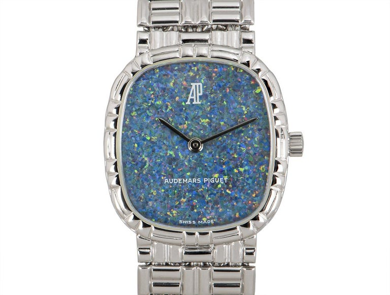 A women's 20mm cocktail dress watch in white gold by Audemars Piguet, featuring a blue opal dial concealed by sapphire glass. The white gold bracelet is equipped with a jewellery style clasp, also in white gold. Fitted with a manual wind