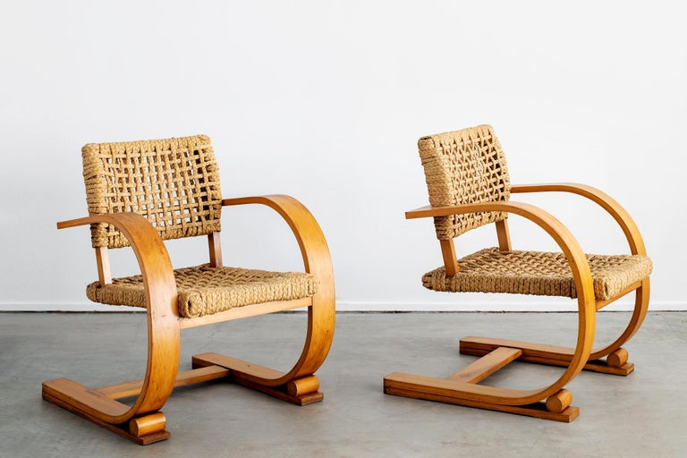 Amazing pair of chairs by Paris designer - Adrien Audoux & Frida Minet. Classic modern French design with rope seats and backs Wide French bent oakwood arms with fantastic patina.  Matching table available - sold separately.