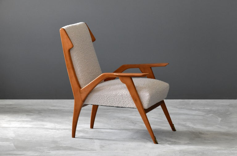 An Italian lounge chair, design attributed to Augusto Romano.   The highly modern wooden frame is further ornamented by brass details. Sourced through an antiquarian in Sicily.