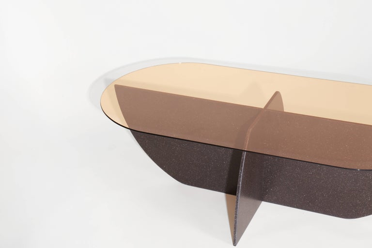 The Aurora coffee table is made from an intersecting curved base and tempered glass top. The solid surface base is a highly sustainable recycled material that is durable and easy to clean. Base and glass are custom machined in the United States.