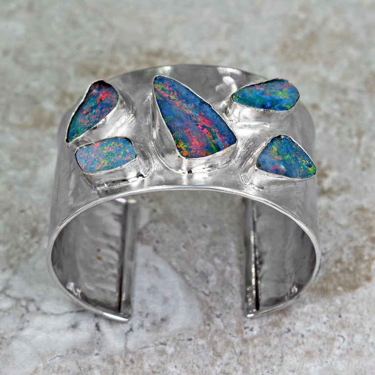 Five, gorgeous Australian Boulder Opals set in a hammered, sterling silver wide cuff bracelet with a brushed finish. Silver cuff is 1.5 inches wide. Inside of bracelet is 2.32 inches in width and bracelet opening is 1.07 inches wide, but is