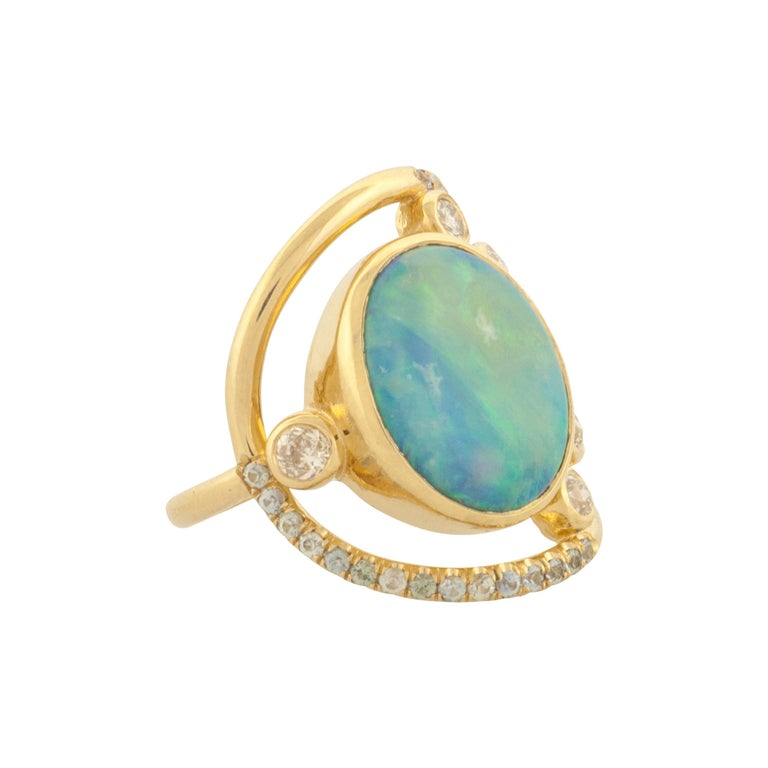 One of a kind stone cluster ring Australian black opal cabochon weighs 4.29ct  6 bezel set, round white diamonds have a total gem weight of .48ct  31 pavé set, blue Montana sapphires have a total gem weight of .37ct  Round wire shank measures