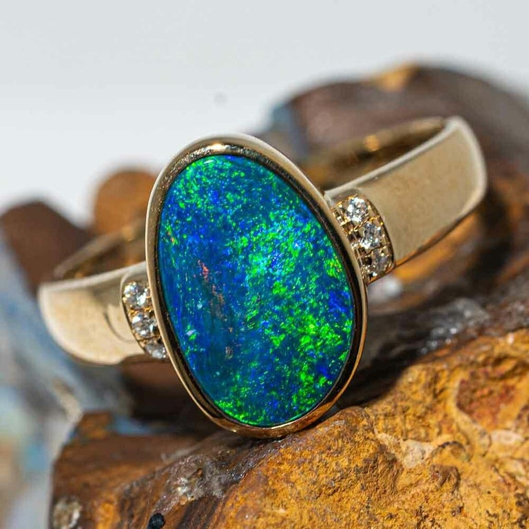 This  Oceanic 14KT Yellow Gold & Diamond Australian Opal Ring  with diamonds at each side and shows a  brilliant blue and green sea colored which flashes that dance and play throughout the precious gemstone. The Solid 14KT Yellow Gold setting